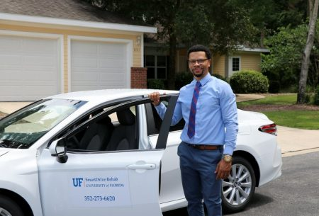 Dr. Luther King standing with SmartDrive car in front of Smart House